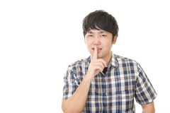 Man placing finger on lips. Portrait of a man making silence gesture stock image