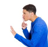 Man placing fingers on lips with shhh sign Stock Photo