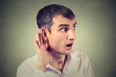 Man placing hand on ear asking someone to speak up or listening carefully to gossip Stock Photo