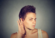 Man placing hand on ear listening carefully to gossip Royalty Free Stock Photography