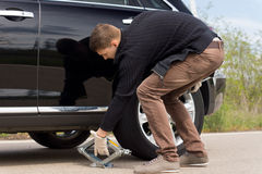 Man placing a hydraulic jack under his car. To raise the vehicle allowing him to change the wheel for a spare following a roadside puncture stock image