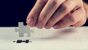 Man placing the last piece in the jigsaw puzzle Royalty Free Stock Photo