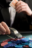 Man placing model car on pile of gambling chips on table, mid section Royalty Free Stock Photo