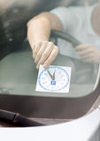 Man placing parking clock on car dashboard Royalty Free Stock Images