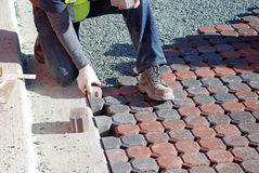 Man Placing Paving Stones. A worker places paving stones cut especially for the edge of a driveway Royalty Free Stock Photo