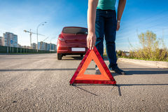 Man placing red triangle sing on road after car crash Royalty Free Stock Images