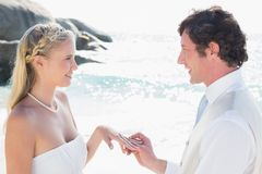 Man placing ring on pretty blonde brides finger Royalty Free Stock Photos