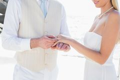 Man placing ring on smiling brides finger Stock Photos