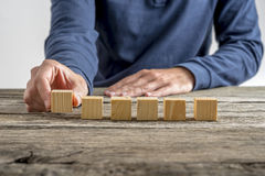 Man placing six blank wooden cubes in a row Stock Image