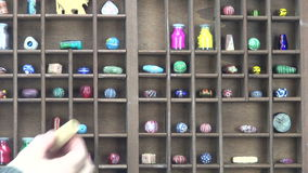 Man placing various objects in shelf. Hand  placing ceramic beads and paint bottles in shelf stock video footage