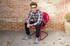 Man In Plaid Long-Sleeved Shirt And Black Pants Sitting On Red Chair Royalty Free Stock Images