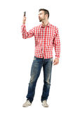Man in plaid shirt checking his smart phone. Royalty Free Stock Photo