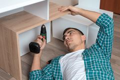 Man in plaid shirt collects furniture lying down stock image