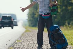 A man in a plaid shirt, dark pants, with an accordion on his shoulders standing by the road and honking, backpack lying. At his feet, close-up Royalty Free Stock Image
