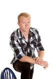 Man in plaid shirt foot up on chair serious Royalty Free Stock Images