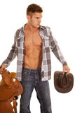 Man plaid shirt hold saddle and hat shirt open. A cowboy holding onto his hat and his sadde with a serious expression stock photography