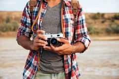 Man in plaid shirt holding old vintage photo camera Stock Photos
