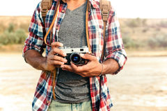 Man in plaid shirt holding old vintage photo camera. Closeup of man in plaid shirt standing and holding old vintage photo camera Royalty Free Stock Image