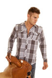 Man plaid shirt holding saddle look to side Royalty Free Stock Photography