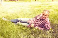 A man in a plaid shirt is resting lying on green grass. Stock Images
