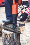 Man in plaid shirt sawing piece of wood on stump Royalty Free Stock Images