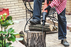 Man in plaid shirt sawing piece of wood on stump Stock Photo