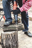 Man in plaid shirt sawing piece of wood on stump Stock Photos