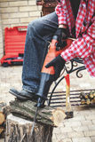 Man in plaid shirt sawing piece of wood on stump Stock Photography
