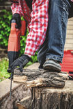 Man in plaid shirt sawing piece of wood on stump Royalty Free Stock Photography