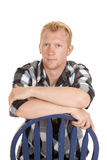 Man in plaid shirt sit on blue chair back serious Royalty Free Stock Image