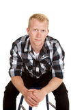 Man in plaid shirt sit lean forward serious Royalty Free Stock Photo