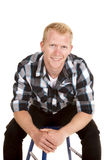Man in plaid shirt sit lean forward smile Stock Images