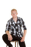 Man in plaid shirt sit looking serious Stock Images