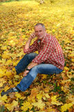 A man in a plaid shirt is sitting in autumn park. Royalty Free Stock Image