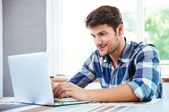 Man in plaid shirt sitting and using laptop at home Royalty Free Stock Photos