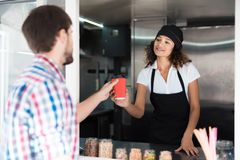 The man in the plaid shirt went to the food truck. He ordered coffee for himself. It is served by beautiful girl seller. The men in the plaid shirt went to the Stock Image