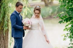 A man in a plaid suit admires his wife`s wedding dress and helps her to keep a bouquet of peonies. The bride corrects stock photos