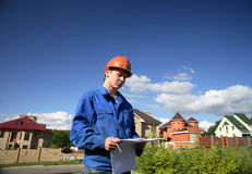 Man with the plan of construction and helmets. On a background of building houses Royalty Free Stock Photos