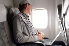 Man in a plane. Mature man with laptop in a plane royalty free stock image