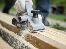 Man planing boards with electric tools, chips flying in all directions. Construction, wood processing stock image
