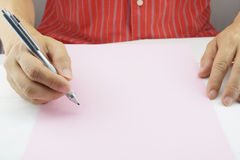 Man planning business on pink paper. Man is planning to do business and present on pink paper Stock Image