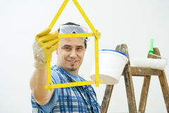 Man planning new home. Man showing yellow folding ruler shaped in form of house. Isolated on white background. Selective focus on man Stock Photo