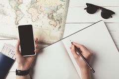 Man planning travel with smartphone and map Royalty Free Stock Photo