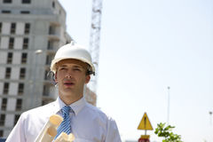 Man with plans on construction site Stock Photo