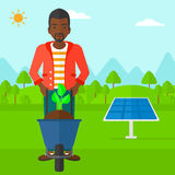 Man with plant and wheelbarrow. An african-american man standing with a plant and soil in a wheelbarrow on a background with solar panels vector flat design Royalty Free Stock Images