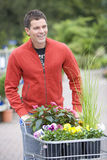 Man with plants in garden center, smiling Stock Photography