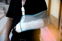 Man with a plaster because broken arm. A man with broken left arm on a sling royalty free stock photo