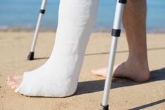 Man with plaster walking on the beach. With the help of crutches Royalty Free Stock Photography