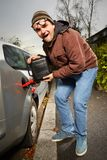 Funny winter time dressed man filling tank of car Stock Image