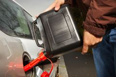 Winter time dressed man filling tank of car from plastic canister Royalty Free Stock Photography